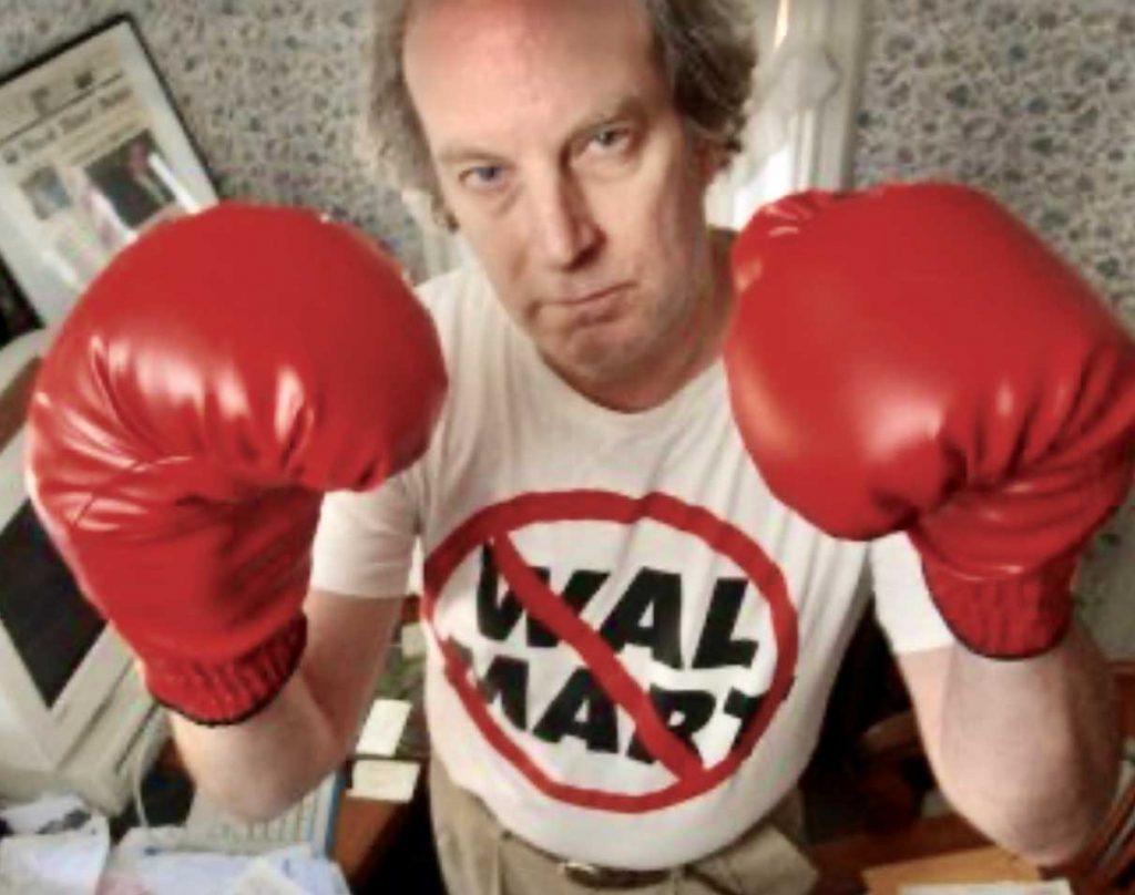 "Al Norman wearing a ""No Wal-Mart"" t-shirt and boxing gloves"