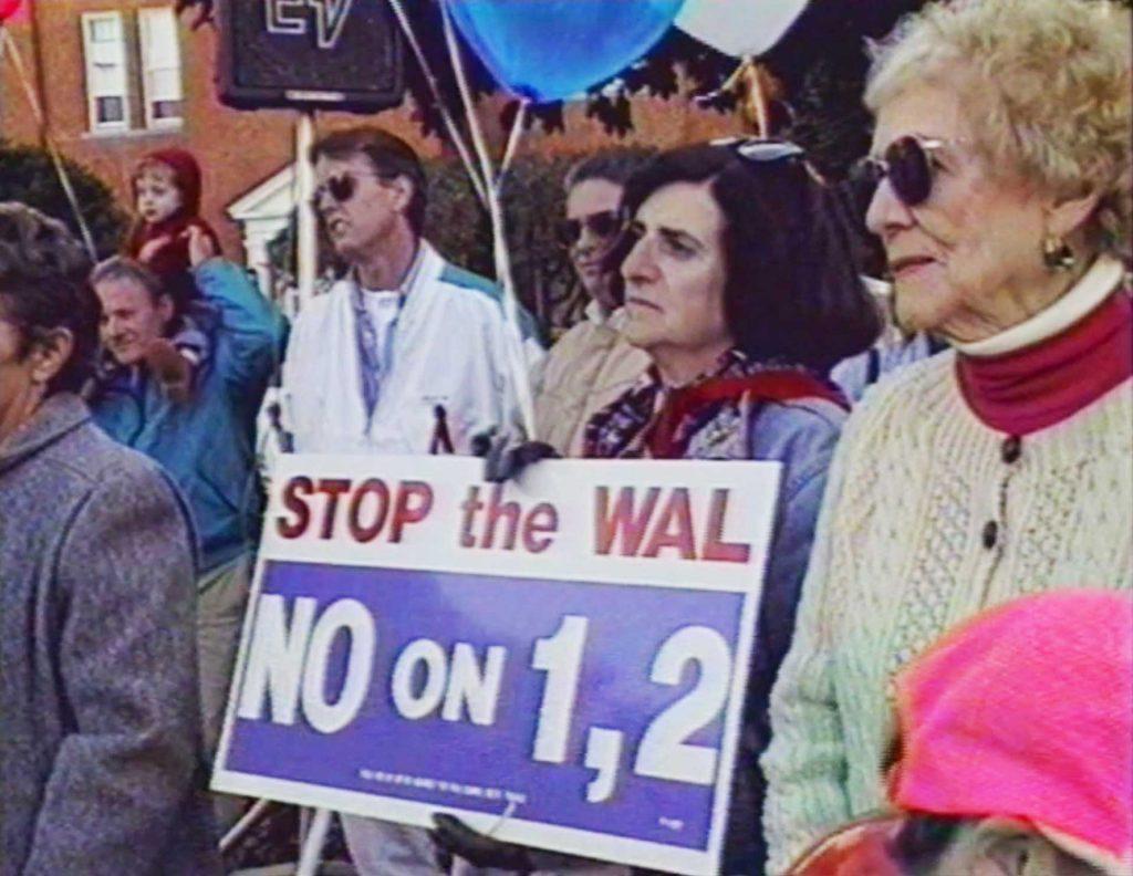 Protestors listen to a speech at an anti-Walmart march