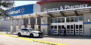 A police car parks in front of a Wal-Mart closed off with caution tape