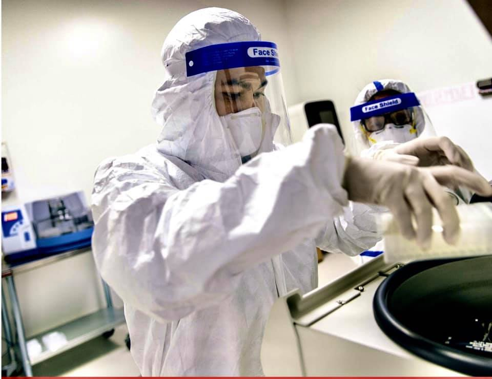 People wearing face shields work with chemicals
