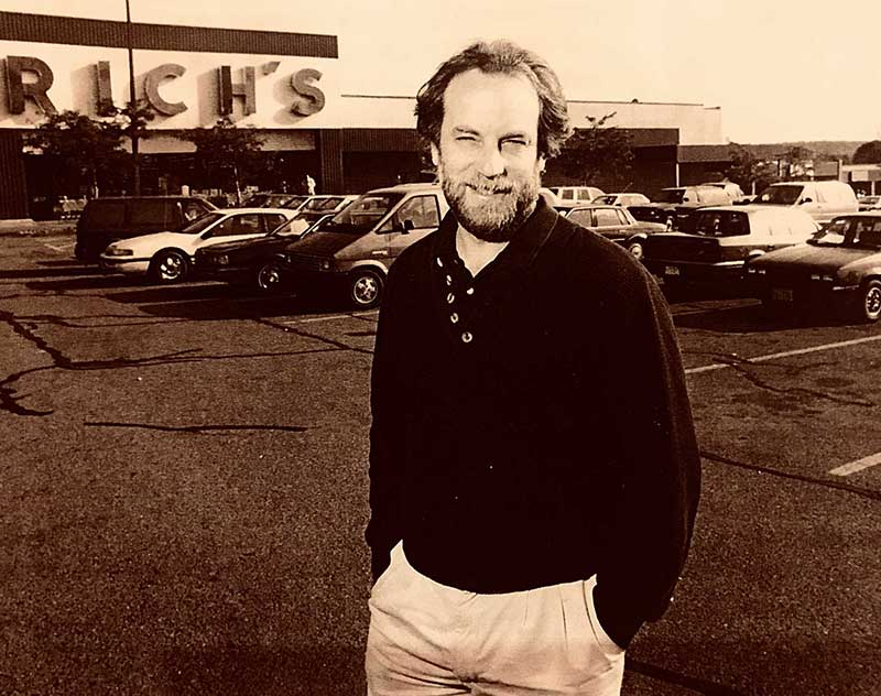 Al Norman poses in a parking lot in front Rich's department store